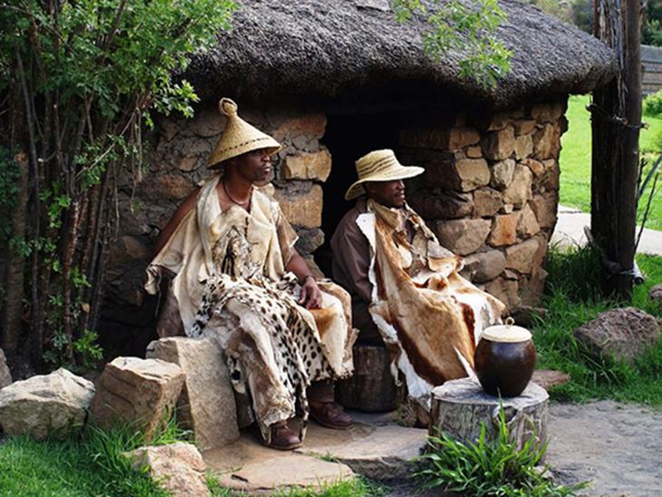Langues parlées : deux hommes assis au pied d'une maison